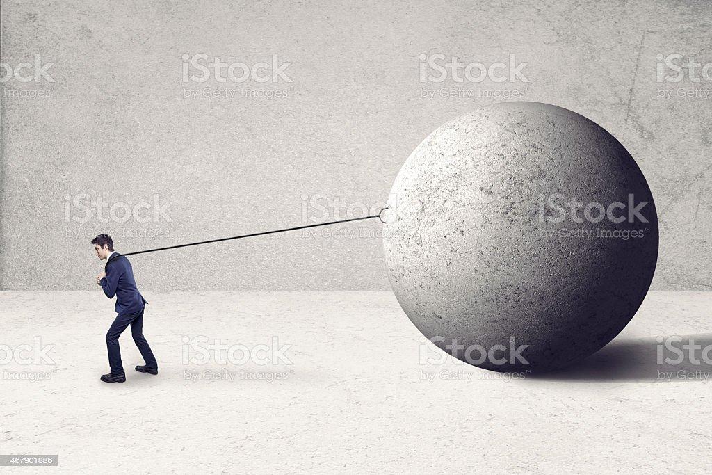 guy pulling big rock ball stock photo