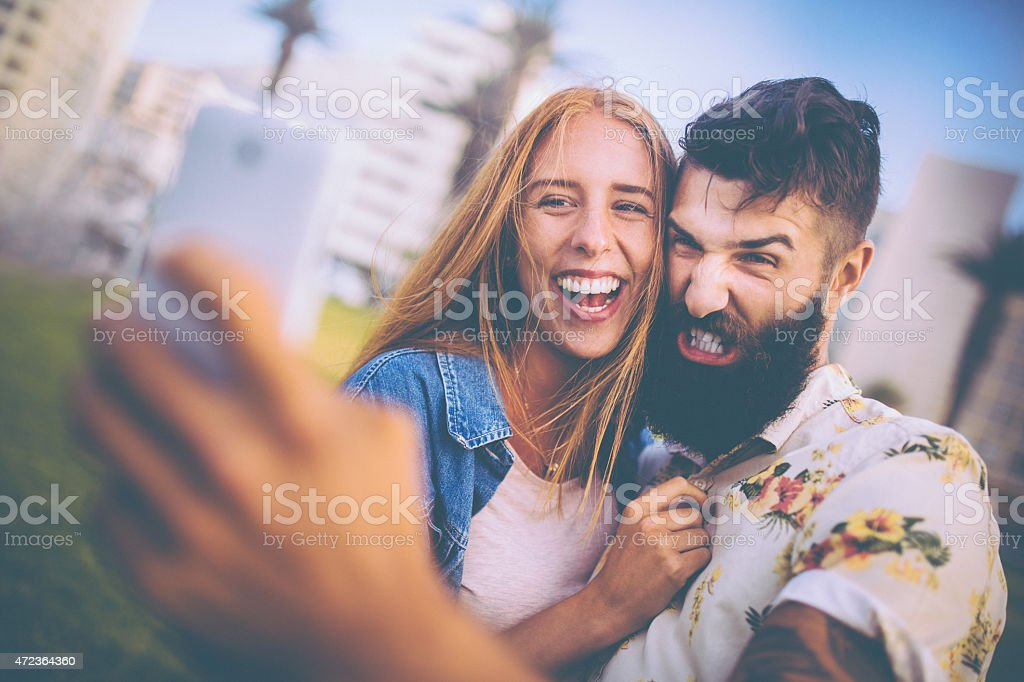 Guy pulling funny face for a selfie with his girlfriend stock photo