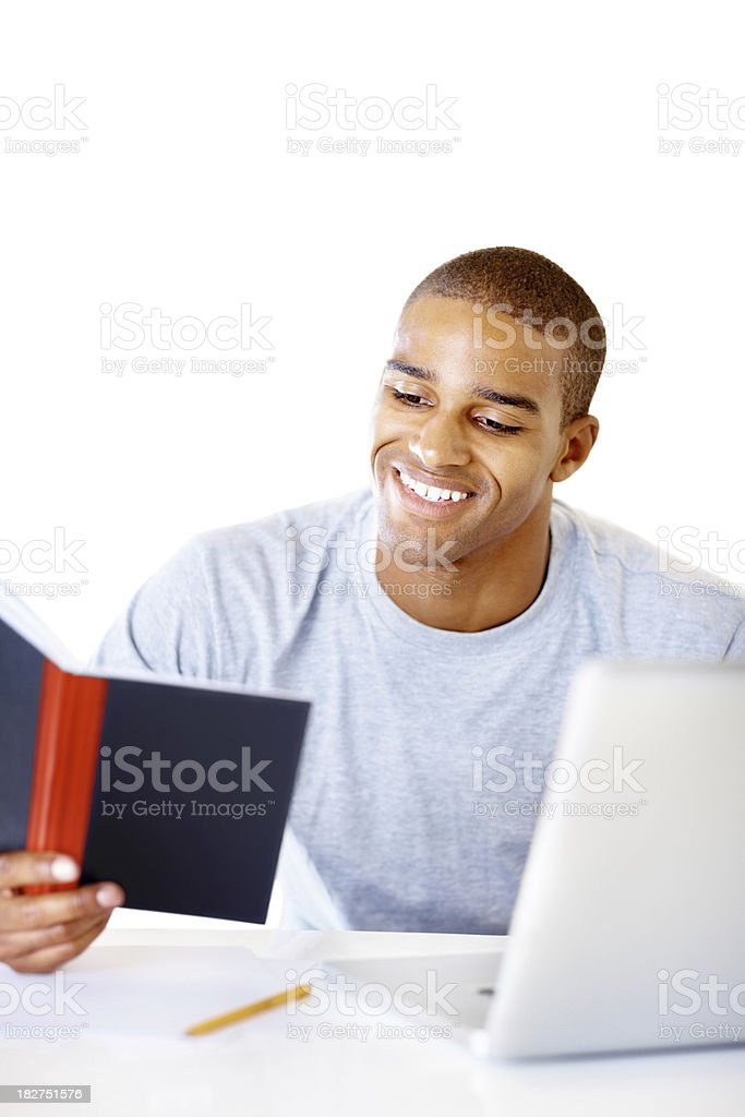 Guy reading book white sitting in front of laptop stock photo