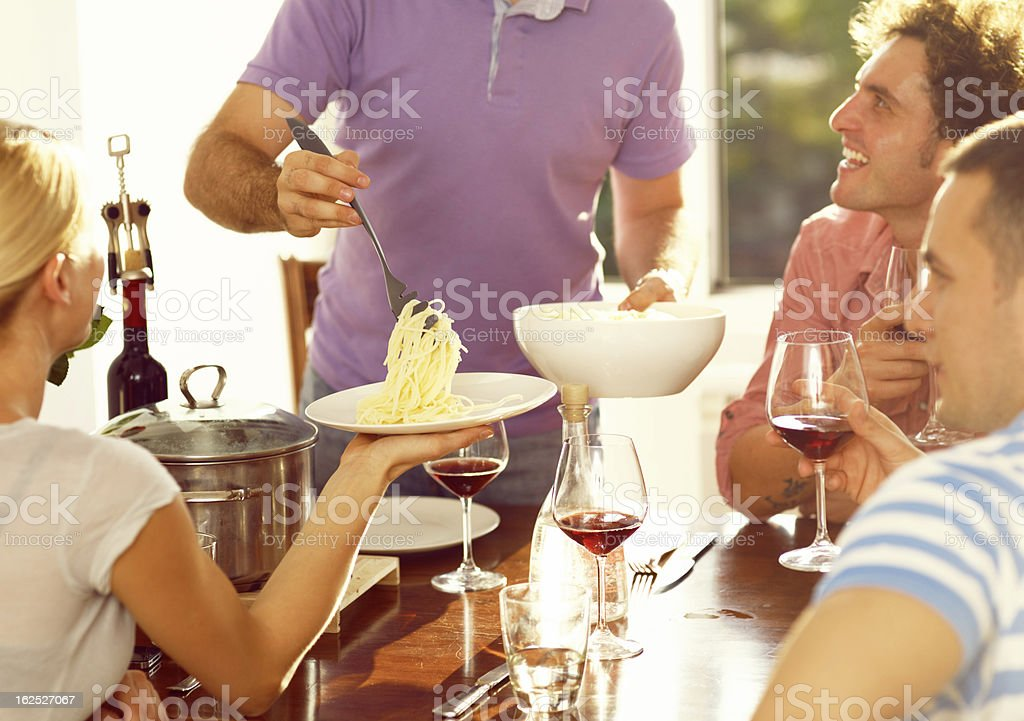Guy serving pasta to his friends royalty-free stock photo