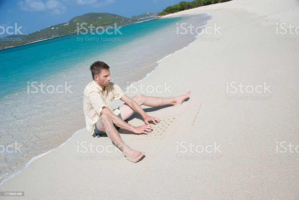 Guy Sits on Beach Typing w Sand Laptop stock photo