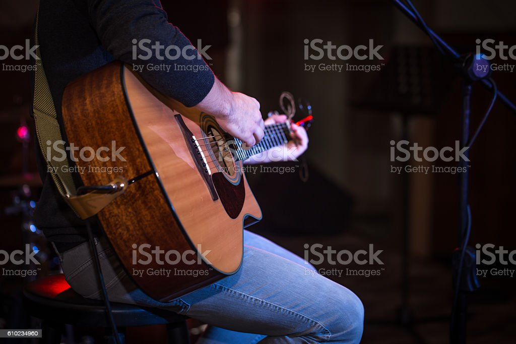 guy sitting in a high chair and playing acoustic guitar stock photo