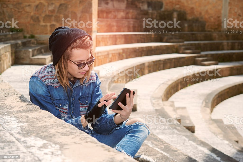 guy sitting on a staircase with tablet warm filter applied stock photo