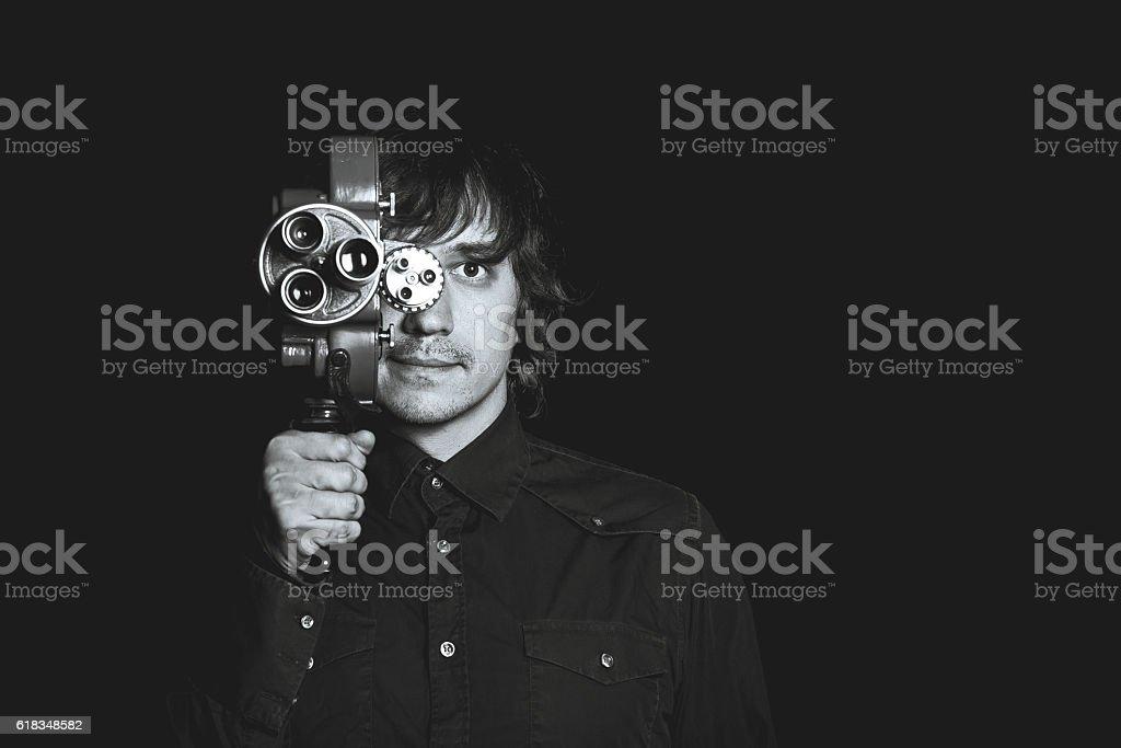 Guy takes on a retro movie camera. Black and stock photo