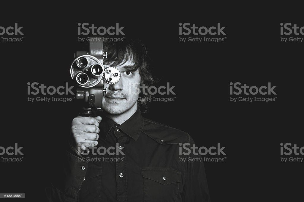 Guy takes on a retro movie camera. Black and stock photo