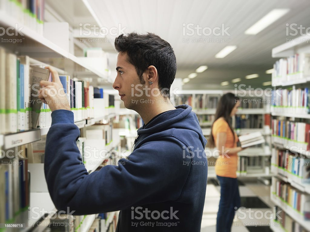 guy taking book from shelf in library royalty-free stock photo