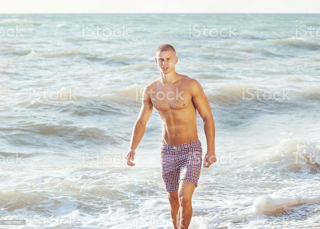 Guy walking on the beach royalty-free stock photo