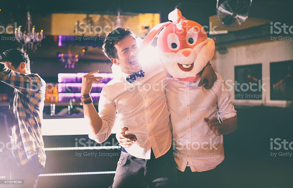 Guy wearing bunny head with friend at party in club stock photo