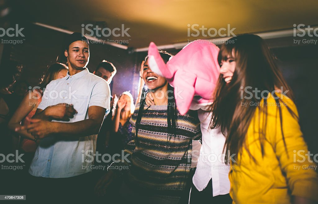Guy with a bunny head with friends at party stock photo