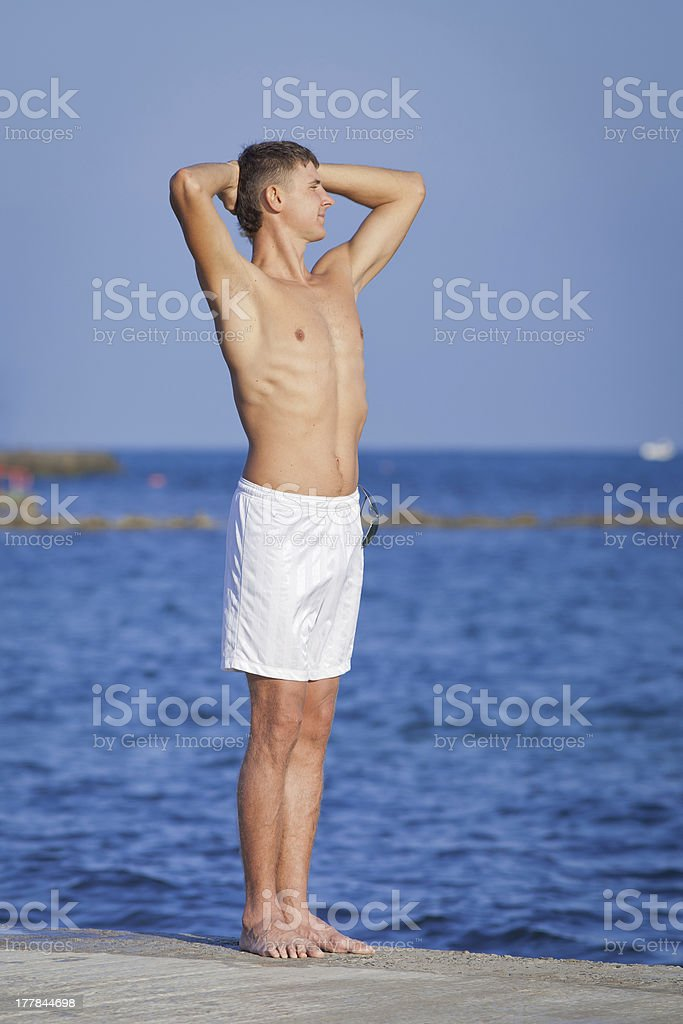 Guy with arms raised standing on pier royalty-free stock photo