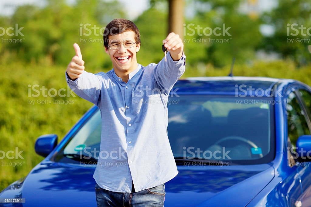 Guy with car key shows thumb up stock photo