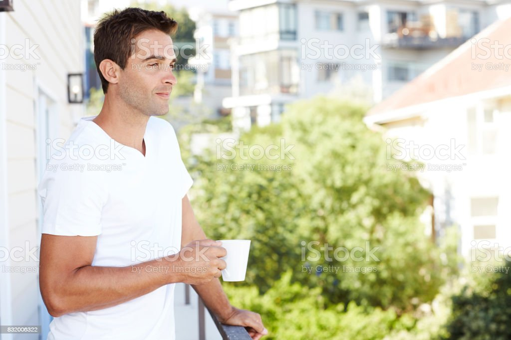 Guy with coffee on balcony stock photo