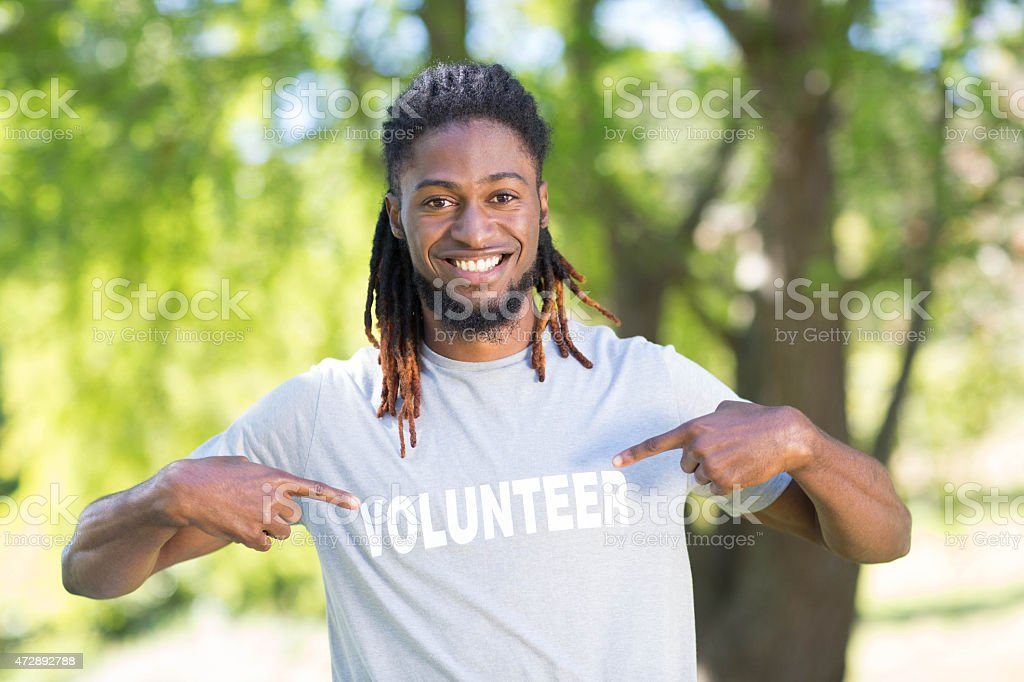 A guy with dreads wearing a volunteer shirt  stock photo