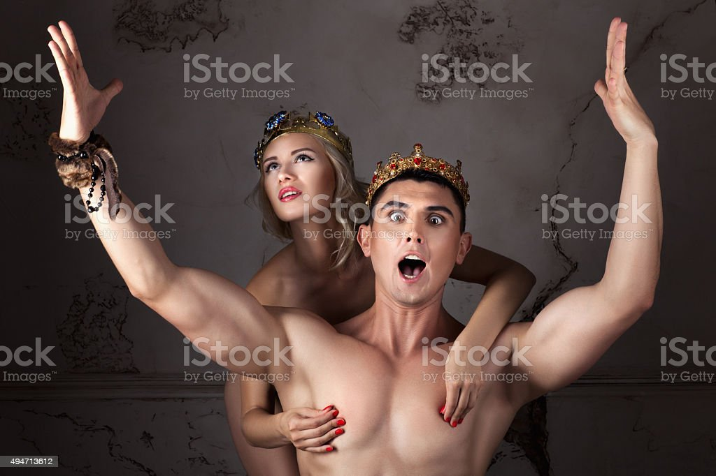 Guy with the crown on head sings his arms. stock photo