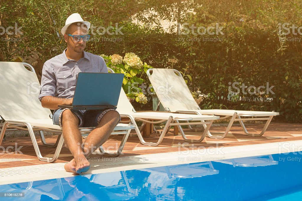 Guy working on laptop next to the swimming pool stock photo