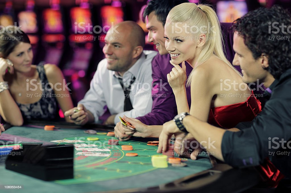 guys and girls playing black jack in casino stock photo