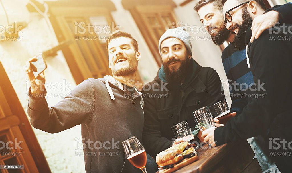 Guys at pub taking selfies. stock photo