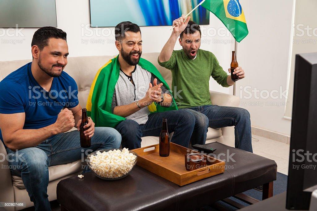 Guys cheering for Brazil on TV stock photo
