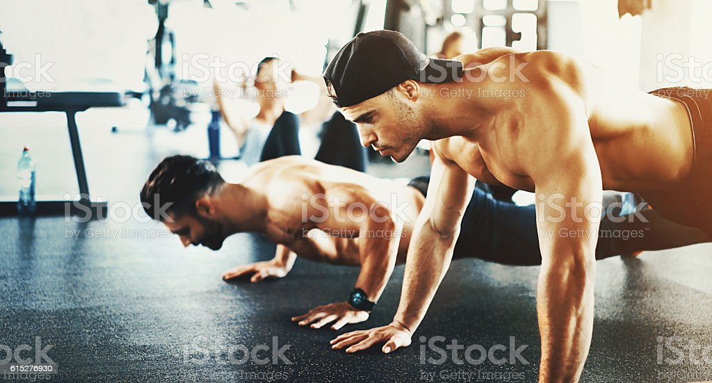 Guys doing push ups in a gym. stock photo