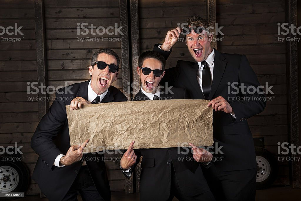 Guys: Men in suits holding blank banner. Copy space. royalty-free stock photo