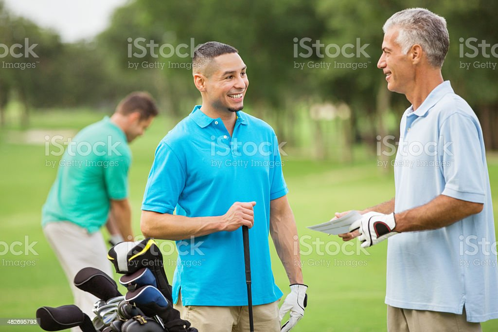 Guys playing a round of golf together on green course stock photo