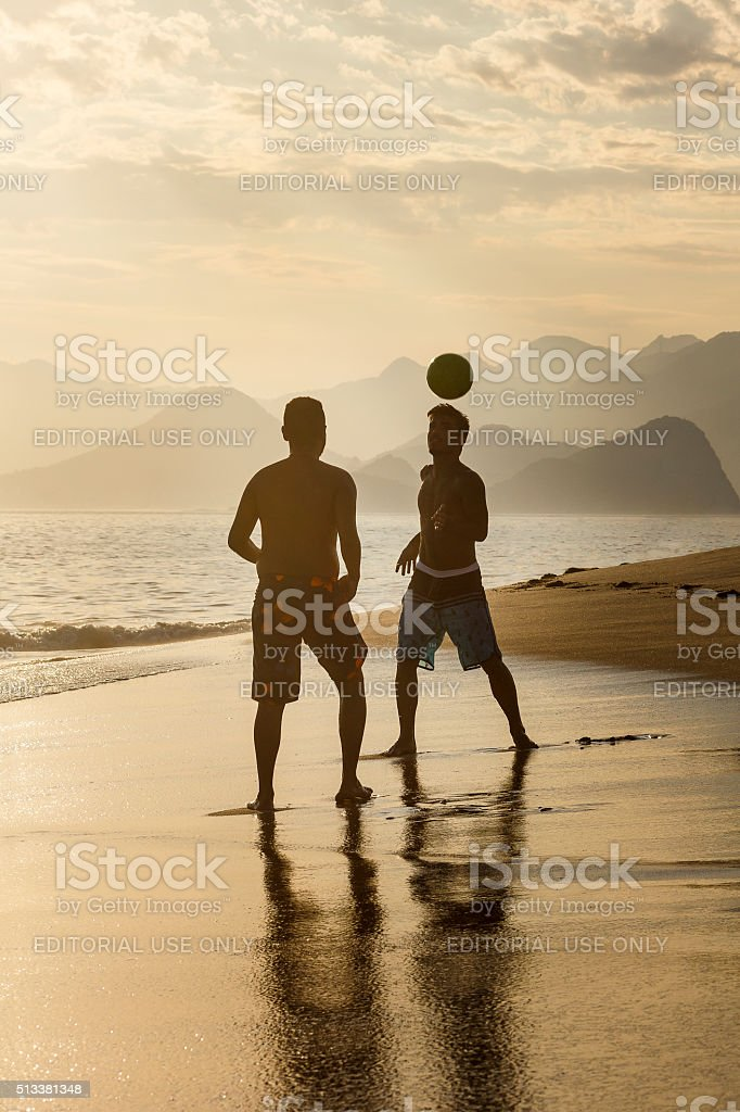 Guys Playing Beach Football at Sunset stock photo