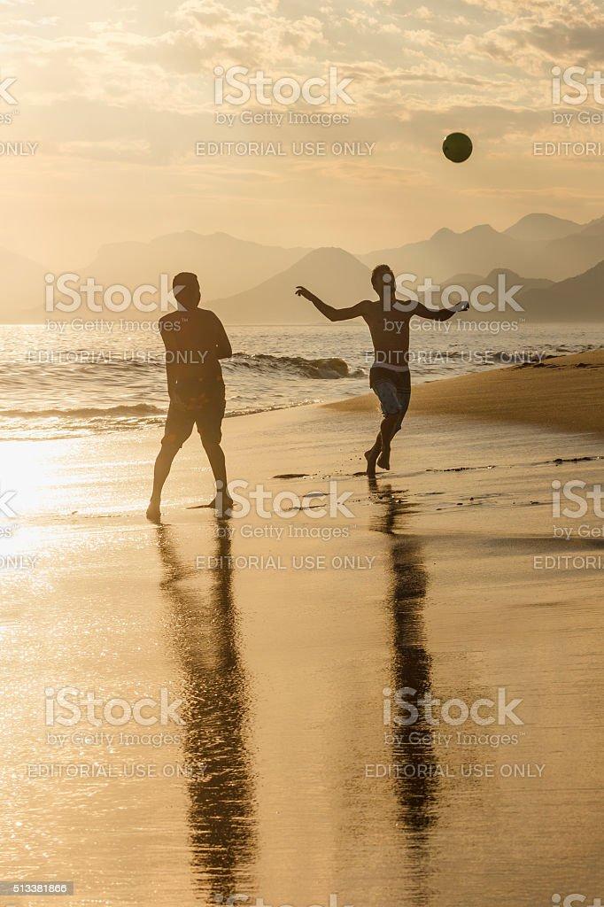 Guys Playing Beach Football at Sunset stock photo