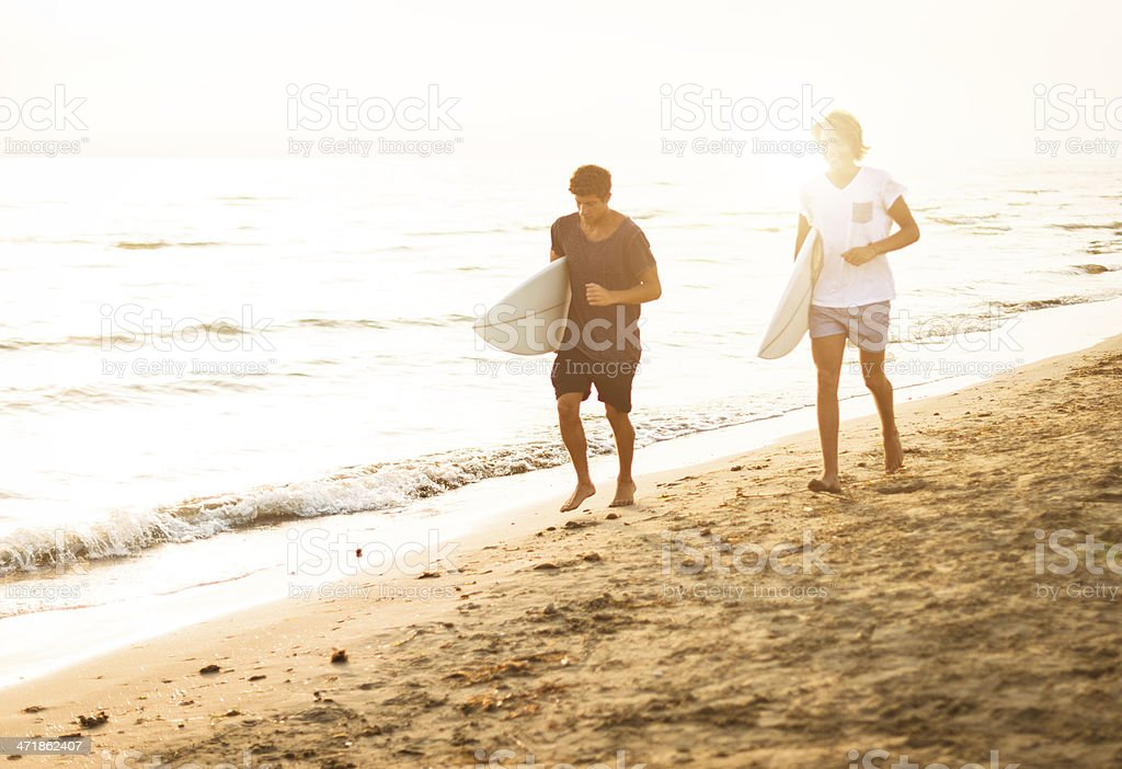 guys running on the beach with surfboard royalty-free stock photo