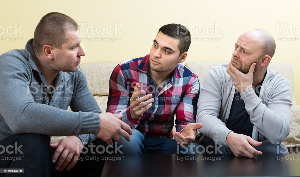 Guys sharing problems at the table stock photo