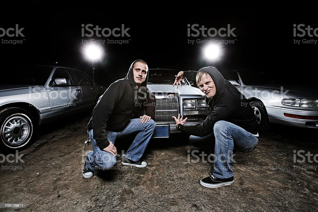 Guys Showing Off Cars in Lot stock photo