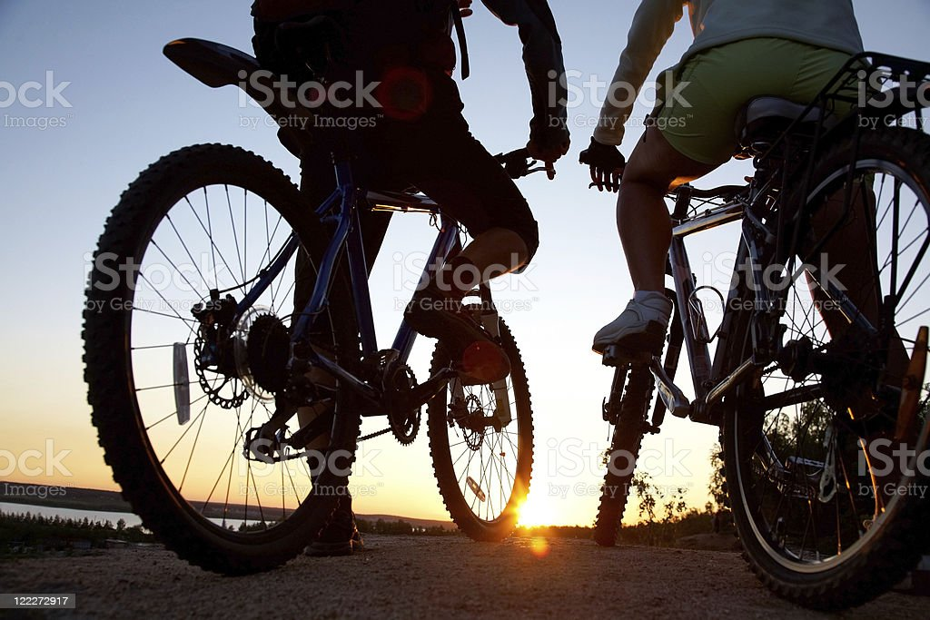 Guys sitting on couple of bicycles watching a sunset royalty-free stock photo