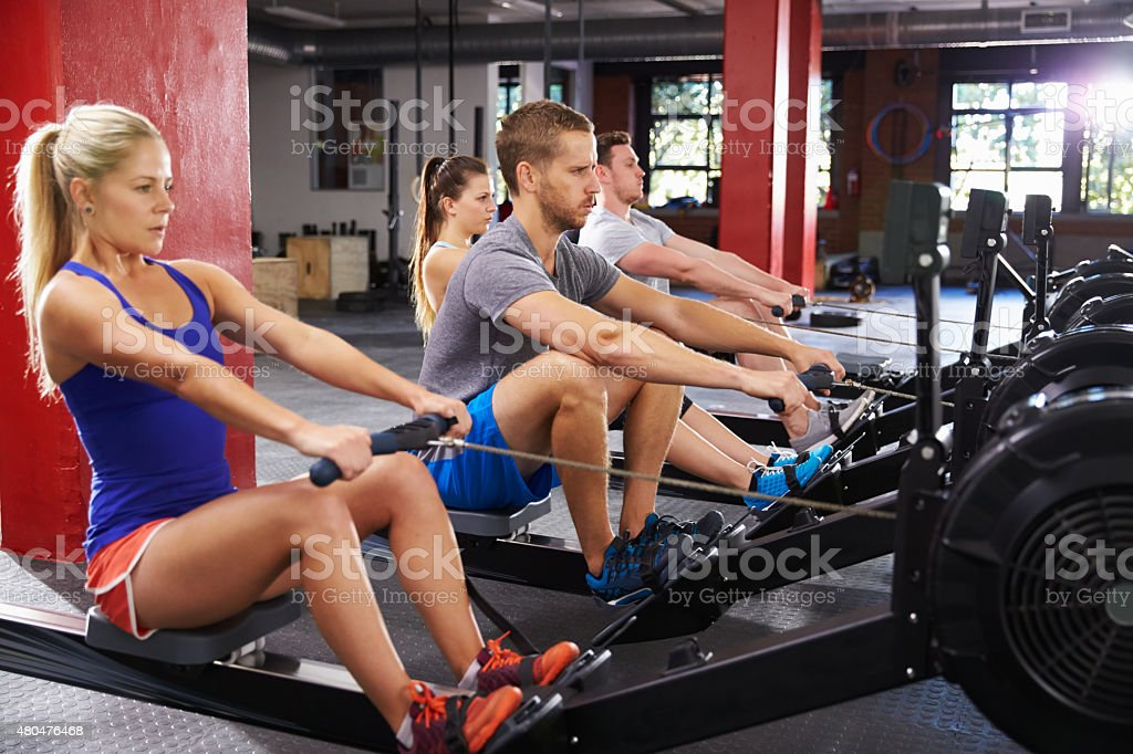 Gym Class Working Out On Rowing Machines Together stock photo