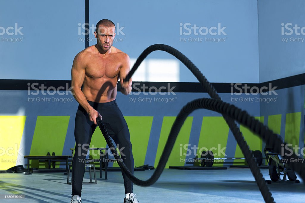 gym contender exercising by battling ropes at the gym stock photo