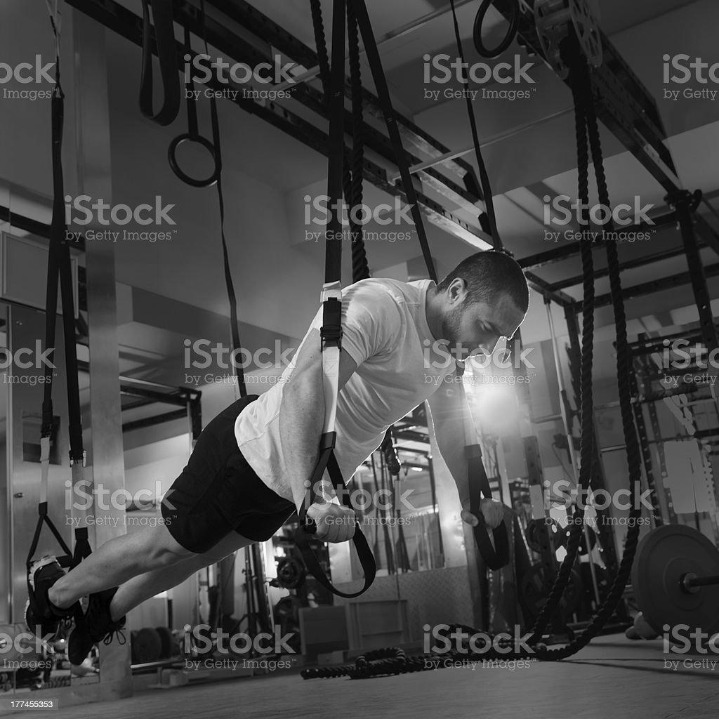 gym fitness TRX push ups man workout stock photo