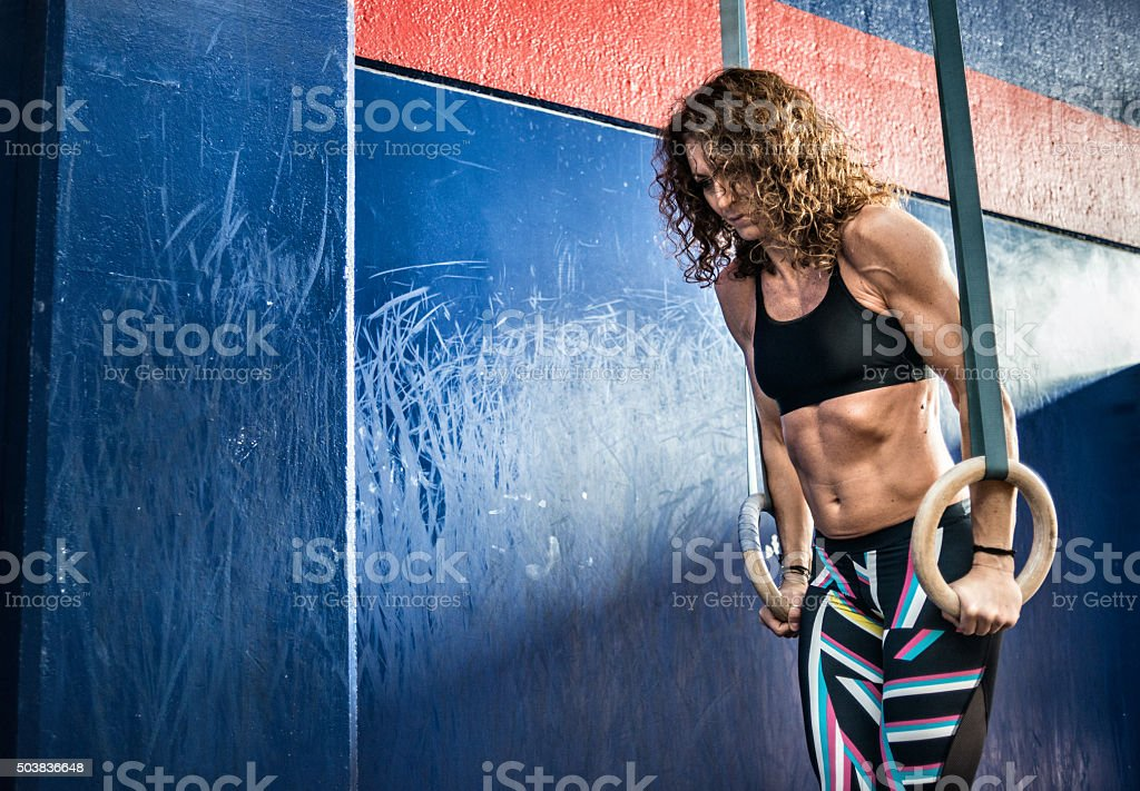 Gym fitness workout: Woman using rings stock photo