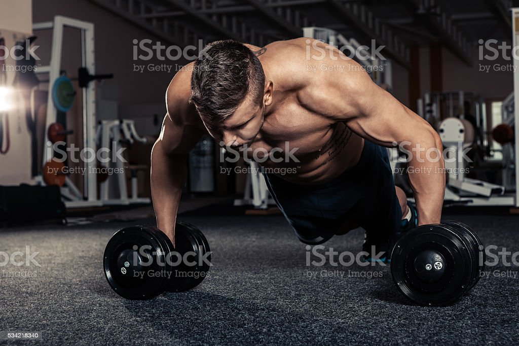 Gym man push-up strength pushup exercise with dumbbell stock photo