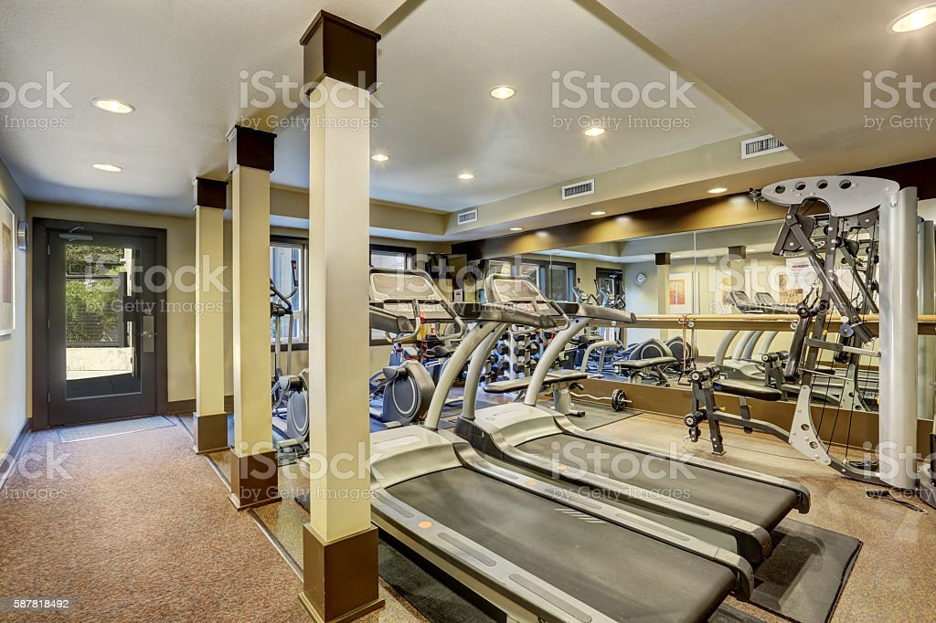 Gym room for residents in apartment building. Different exercise equipments stock photo