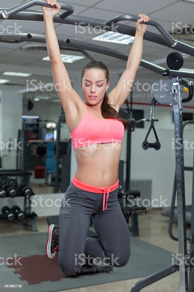 gym toes to bar woman pull-ups stock photo