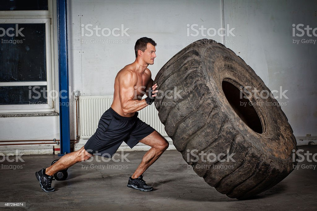 gym training - man flipping tire stock photo