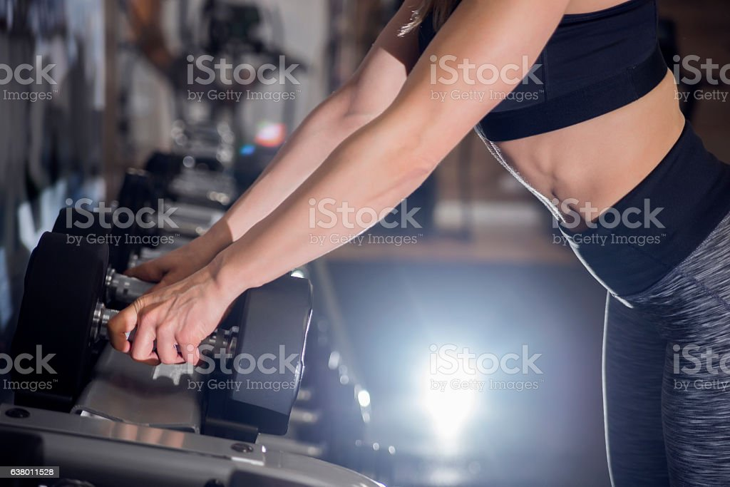 Gym woman Choosing Weight, rack with metal dumbbells stock photo