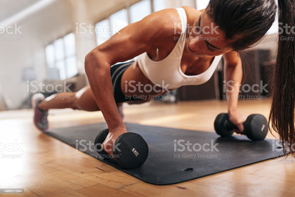Gym woman doing pushups on dumbbells stock photo