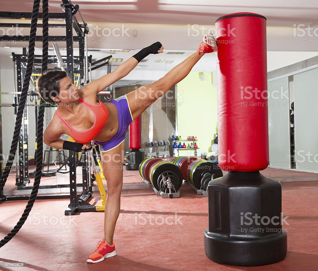 gym woman kick boxing with red punching bag stock photo