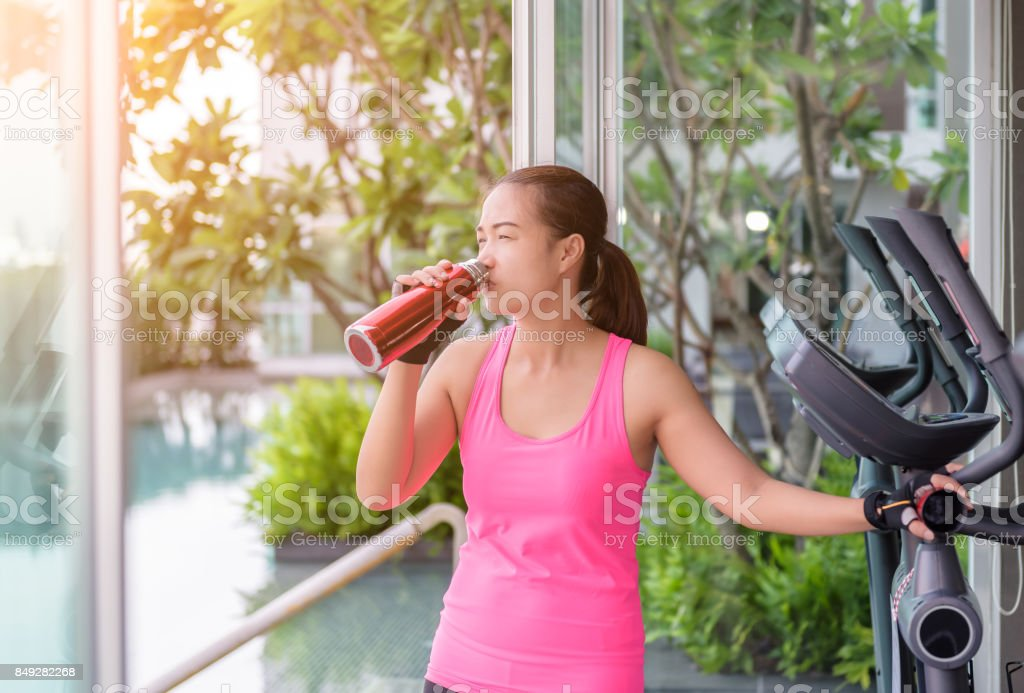 Gym woman working out drinking water at fitness center stock photo