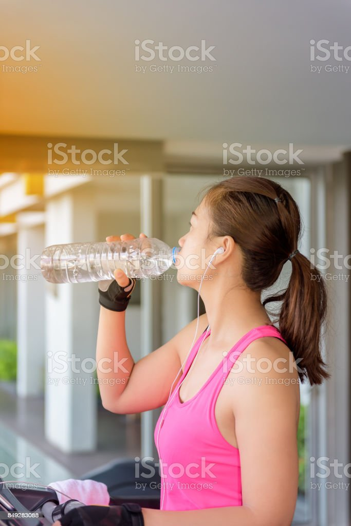 Gym woman working out drinking water by moonwalker fitness machines. stock photo