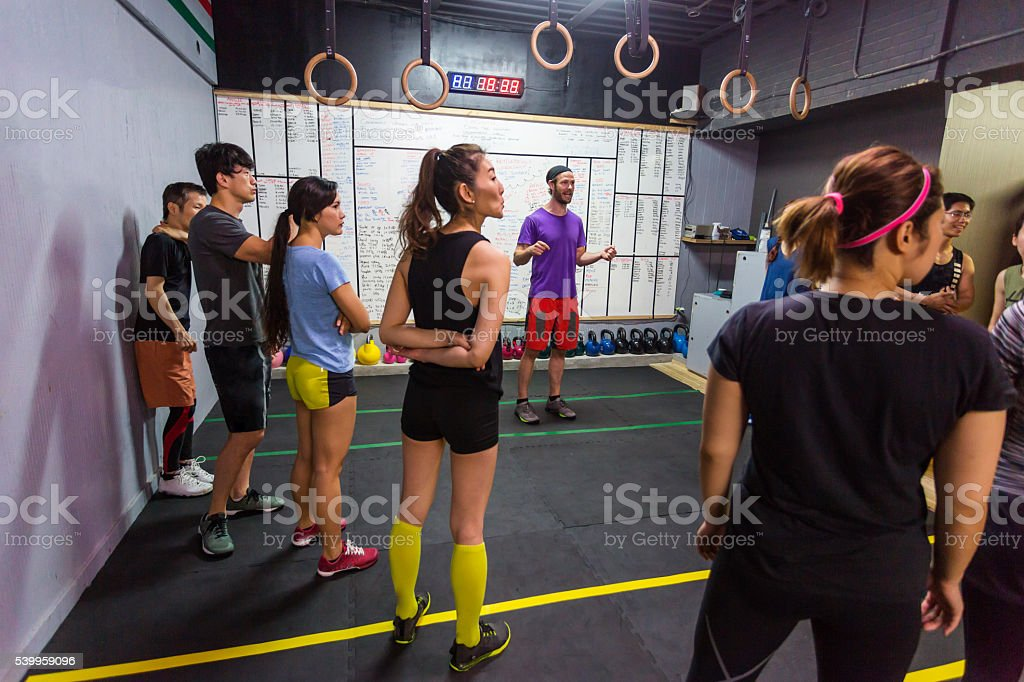 Gym Workout Class Listens While Coach Gives Cross Training Instructions stock photo