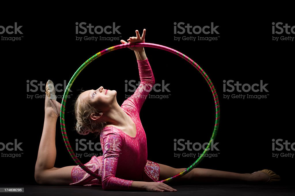 Gymnast girl with hula hoop isolated on black background royalty-free stock photo