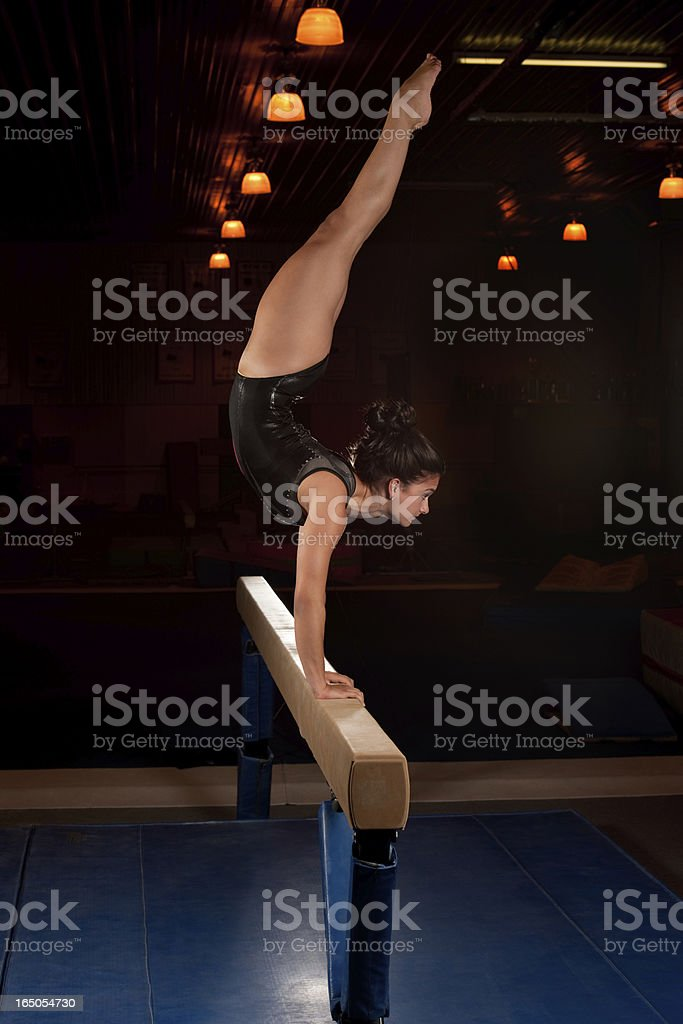 Gymnast in a handstand on a balance beam in a dimly lit room stock photo