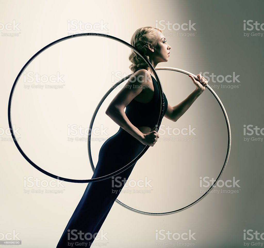 Gymnast in black skin-tight dress with two gymnastic hoop stock photo
