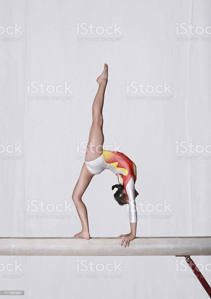 Gymnast performing tricks on a balance beam stock photo