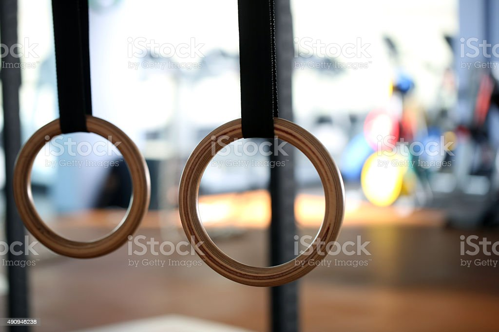 Gymnastic rings hanging at cross fitness gym. Close up stock photo
